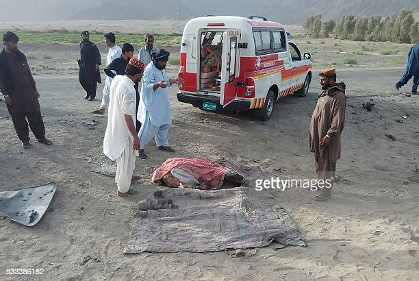 This photograph taken on May 21 2016 shows Pakistani local residents gathering around an unidentified dead body near a destroyed vehicle hit by a...