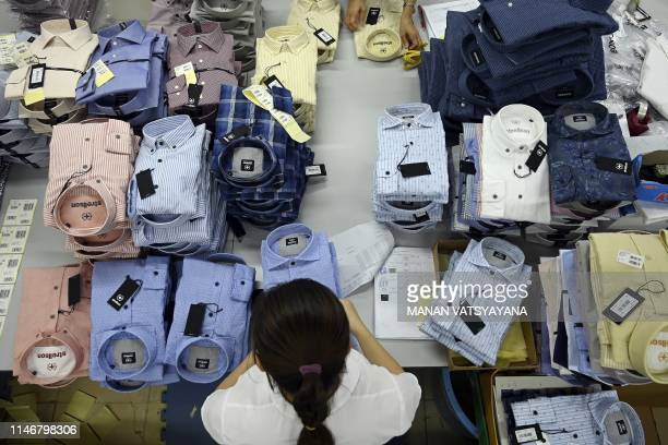 This photograph taken on May 24 2019 shows a garment factory worker packing shirts in a factory in Hanoi From socks and sneakers to washing machines...