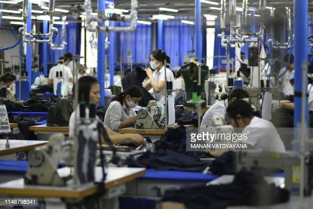 This photograph taken on May 24 2019 shows garment factory workers making men's suits in a factory in Hanoi From socks and sneakers to washing...