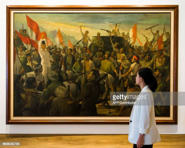 This photograph taken on November 1 2017 shows a woman walking past a painting by Dullah titled 'Revolutionary War' at the Museum of Modern and...