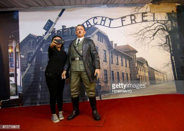This photograph taken on November 10 2017 shows an Indonesian woman take a selfie with a lifesize wax sculpture of Adolf Hitler at a museum in...