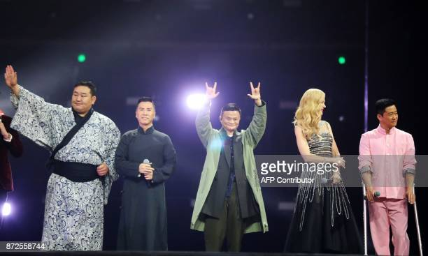 This photograph taken on November 10 shows Chairman of Alibaba Jack Ma as he greets spectators with Mongolia's former sumo wrestler Dagvadorj...