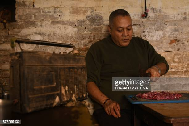 This photograph taken on November 14 2017 shows a Nepali butcher listening to the radio while working at his shop in Bhaktapur some 12km southeast of...