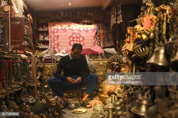 This photograph taken on November 14 2017 shows a Nepali man eating while listening to the radio at a shop in Bhaktapur some 12km southeast of...