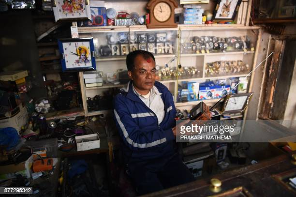 This photograph taken on November 14 2017 shows a Nepali man listening to the radio at a his shop in Bhaktapur some 12km southeast of Kathmandu With...