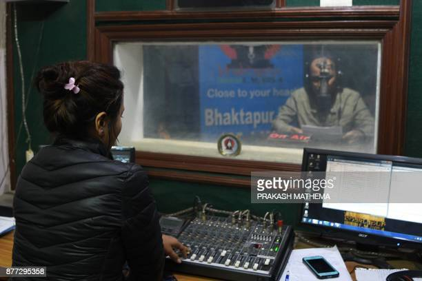 This photograph taken on November 14 2017 shows a Nepali radio broadcaster and a sound technician at a radio station in Bhaktapur some 12km southeast...