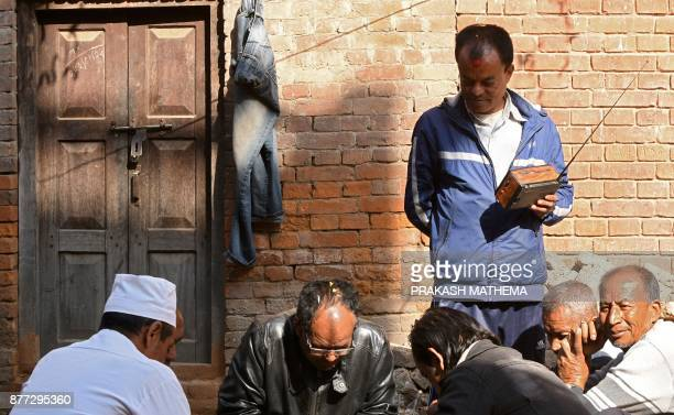 This photograph taken on November 14 2017 shows Nepali men listening to the radio while playing chess in Bhaktapur some 12km southeast of Kathmandu...