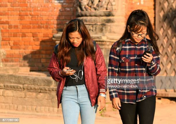 This photograph taken on November 14 2017 shows Nepali women listening to the radio with their mobile phones in Bhaktapur some 12km southeast of...