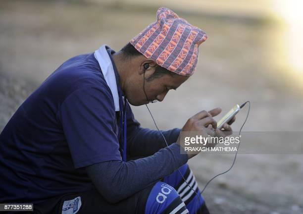 This photograph taken on November 18 2017 shows A Nepali man listening to the radio with his mobile phones in Dhankuta some 400 km east of Kathmandu...