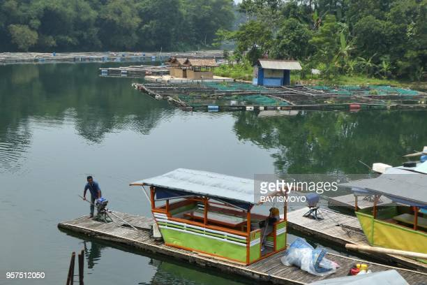 This photograph taken on November 2 2017 shows a man at the helm of a floating restaurant on a lake connected to land under development for a theme...