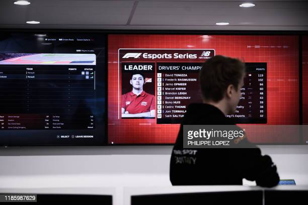 This photograph taken on November 25 shows member of the esport team Vitality Cedric Thome of Germany looking at screens showing standings of the...