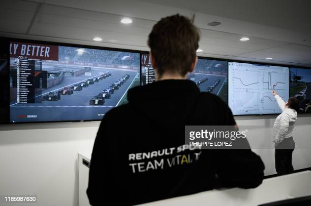 This photograph taken on November 25 shows member of the esport team Vitality Cedric Thome of Germany looking at screens showing technical data...