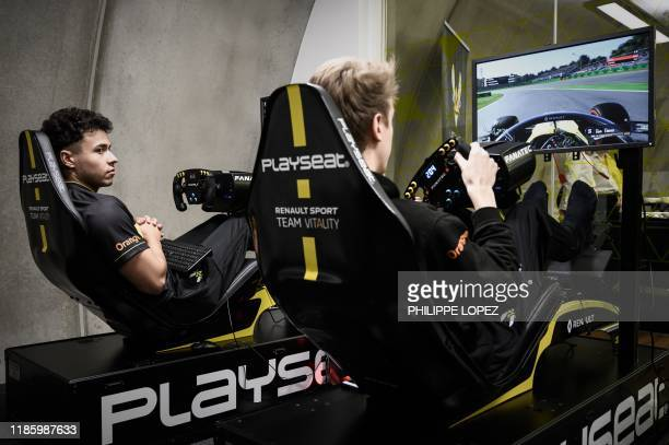 This photograph taken on November 25 shows members of the esport team Vitality Simon Weigang and Cedric Thome both of Germany as they demonstrate...