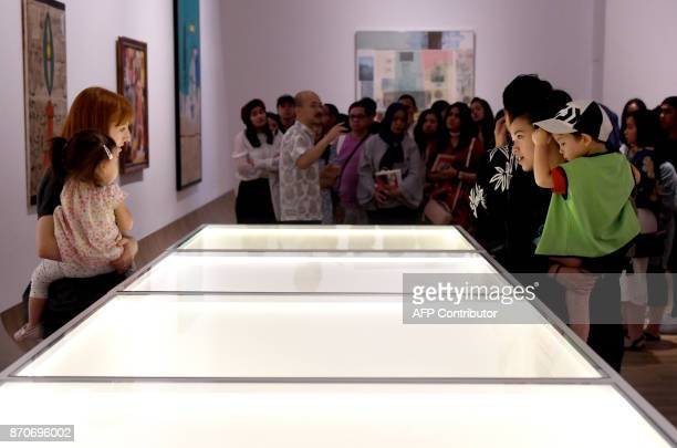This photograph taken on November 5 2017 shows visitors admiring artworks on display at the Museum of Modern and Contemporary Art in Nusantara in...