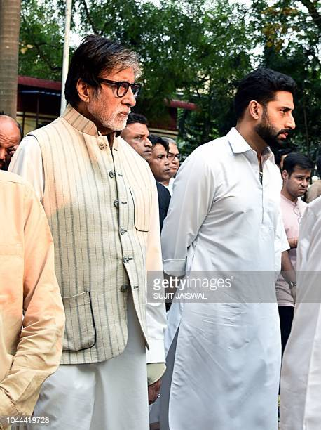 This photograph taken on October 1 shows Indian Bollywood actor Amithabh Bachchan and Abhishek Bachchan attending the funeral Krishna Raj Kapoor wife...