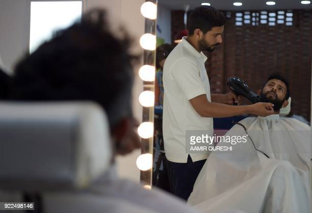 This photograph taken on October 10 2017 shows a male hairdresser blowdrying a customer's beard at a men's salon in Islamabad Nails are buffed...