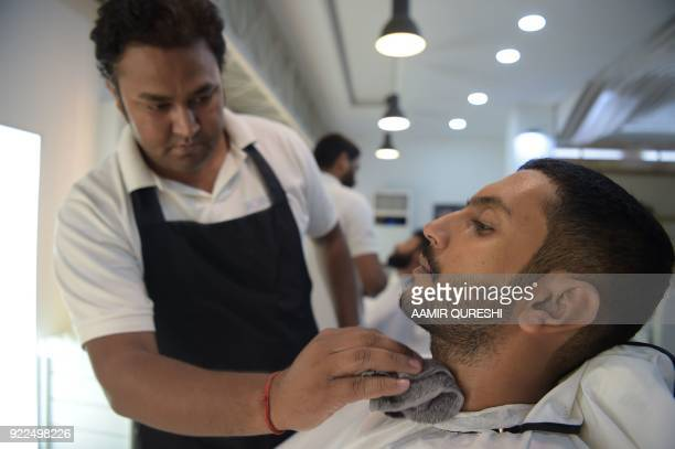 This photograph taken on October 10 2017 shows a male hairdresser trimming a customer's beard at a men's salon in Islamabad Nails are buffed...