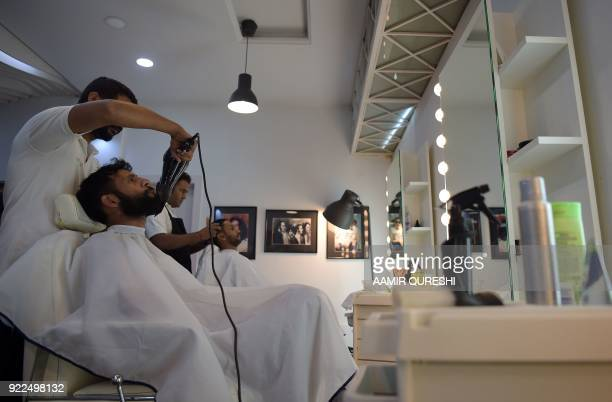 This photograph taken on October 10 2017 shows a male hairdresser blowdrying customer's beard at a men's salon in Islamabad Nails are buffed...