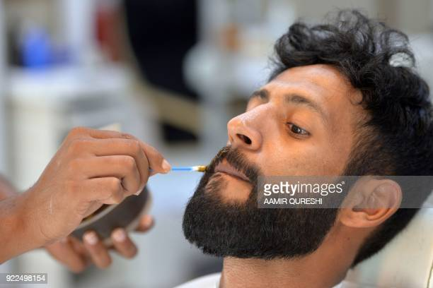 This photograph taken on October 10 2017 shows a male hairdresser applying colour on the moustache of a customer at a men's salon in Islamabad Nails...