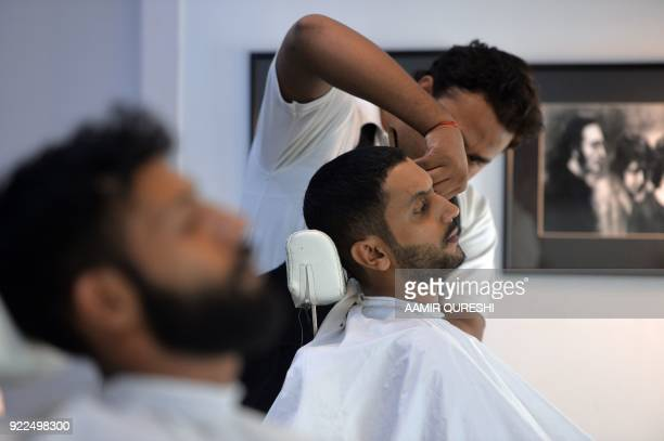 This photograph taken on October 10 2017 shows a male hairdresser cutting the hair of a customer at a men's salon in Islamabad Nails are buffed...