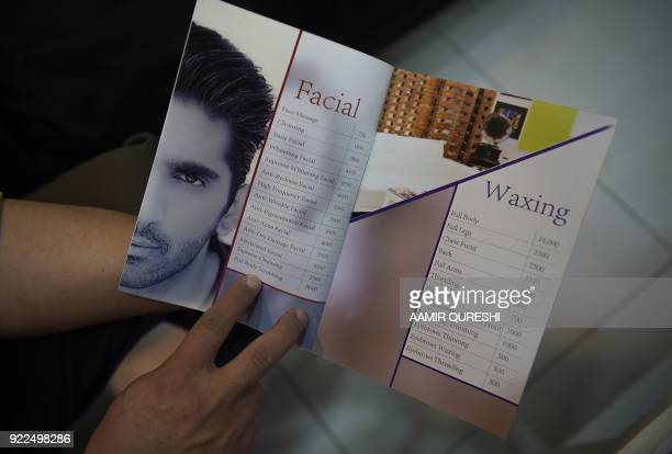 This photograph taken on October 10 2017 shows a Pakistani customer checking a price list for services at a men's salon in Islamabad Nails are buffed...