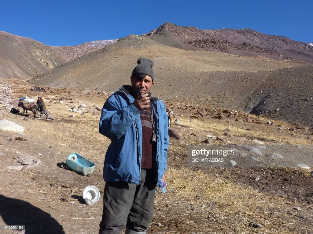 This photograph taken on October 10, 2017 shows Afghan Wakhi nomad man Askar Shah talking on his walkie-talkie in the Wakhan Corridor in Afghanistan. The region is so remote that its residents, known as the Wakhi - a tribe of roughly 12,000 nomadic people who populate the area - are untouched by decades of conflict devastating their country. / AFP PHOTO / Gohar ABBAS / TO GO WITH Afghanistan-Wakhan-Taliban-war,FEATURE by Gohar Abbas