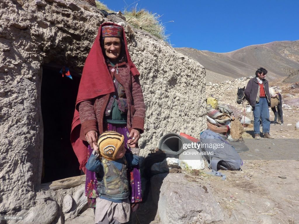This photograph taken on October 10, 2017 shows Afghan Wakhi nomadic woman Sultan Begium standing with her grandson outside her mud home in the Wakhan Corridor in Afghanistan. The region is so remote that its residents, known as the Wakhi - a tribe of roughly 12,000 nomadic people who populate the area - are untouched by decades of conflict devastating their country. / AFP PHOTO / Gohar ABBAS / TO GO WITH Afghanistan-Wakhan-Taliban-war,FEATURE by Gohar Abbas