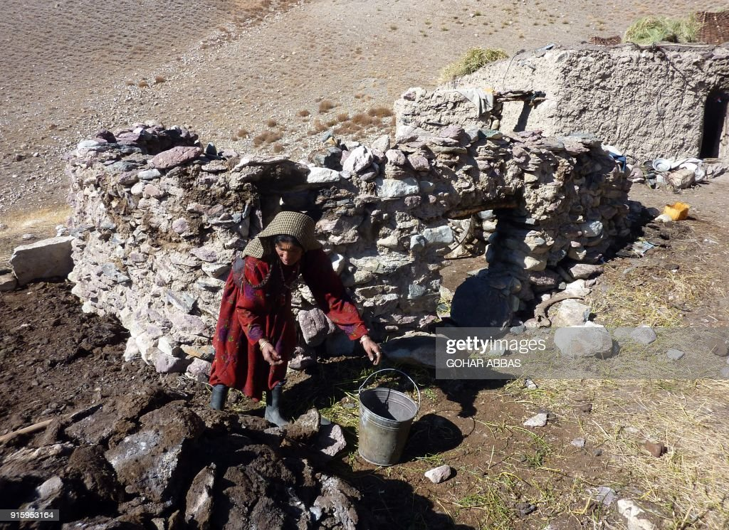 This photograph taken on October 10, 2017 shows Afghan Wakhi nomadic woman Nobot Begium collecting yak dungs that is using for fire fuel outside an animal pen in the Wakhan Corridor in Afghanistan. The region is so remote that its residents, known as the Wakhi - a tribe of roughly 12,000 nomadic people who populate the area - are untouched by decades of conflict devastating their country. / AFP PHOTO / Gohar ABBAS / TO GO WITH Afghanistan-Wakhan-Taliban-war,FEATURE by Gohar Abbas