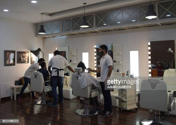 This photograph taken on October 10 2017 shows male hairdressers working with their customers at a men's salon in Islamabad Nails are buffed...