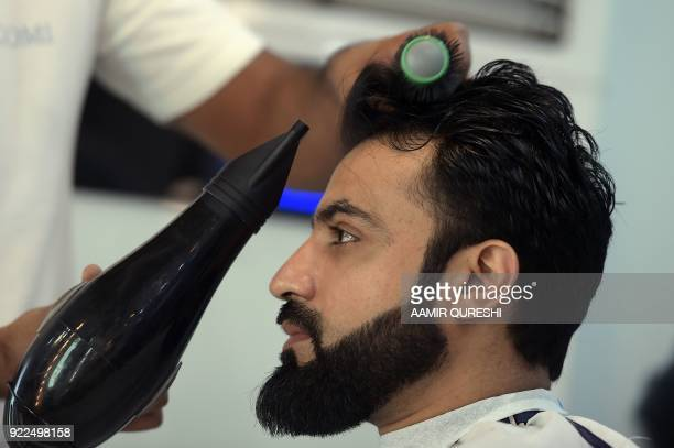 This photograph taken on October 12 2017 shows a male hairdresser blowdrying a customer's hair at a men's salon in Islamabad Nails are buffed...