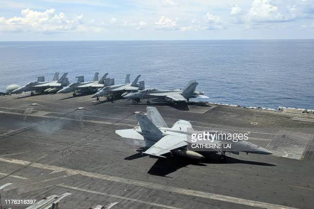 This photograph taken on October 16 2019 shows a US Navy F/A18 Super Hornets multirole fighter landing on the flight deck of USS Ronald Reagan...