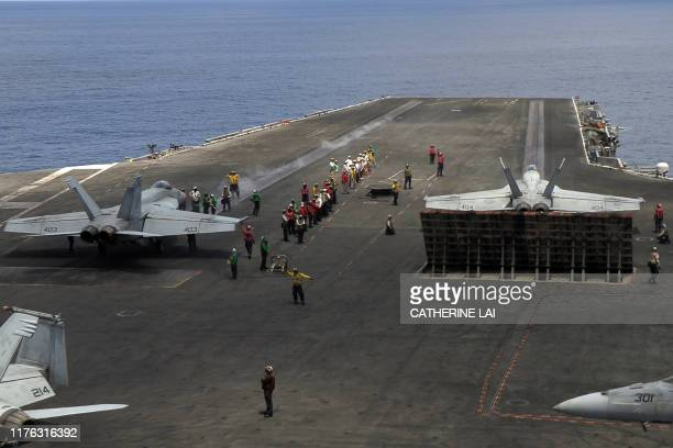 This photograph taken on October 16 2019 shows US Navy F/A18 Super Hornets multirole fighters preparing to take off from the flight deck of USS...