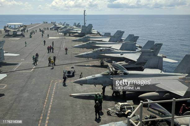 This photograph taken on October 16, 2019 shows US Navy F/A-18 Super Hornets multirole fighters and an EA-18G Growler electronic warfare aircraft on...