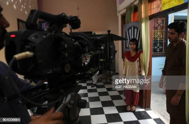 This photograph taken on October 18 shows Pakistani actress Fatiam Shah Jeelani and actor Imran Ashraf filming the drama serial 'Mein Maa Nahi Banna...