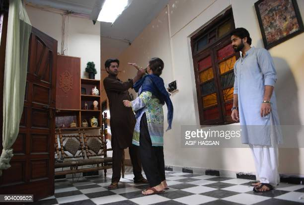 This photograph taken on October 18 shows Pakistani actress Rubina Ashraf and actors Ali Abbas and Imran Ashraf taking part in the filming of a scene...