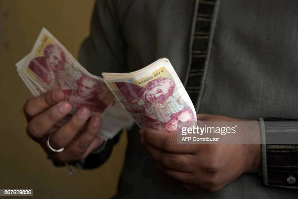 This photograph taken on October 19 2017 shows a Pakistani Kashmiri foreign currency dealer counting British pound notes at a remittance shop in the...