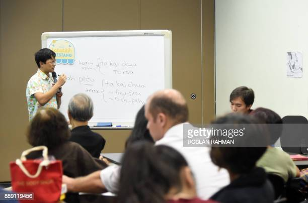 This photograph taken on October 19 2017 shows Kevin Martens Wong 25yearold linguist tutor conducting Kristang language class at the national...