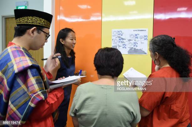 This photograph taken on October 19 2017 shows students from various cultures in a group discussion during their Kristang language class session at...