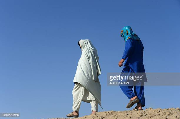 This photograph taken on October 31, 2016 shows an Afghan boy , who was held as a child sex slave, as he walks with a relative at a unidentified...