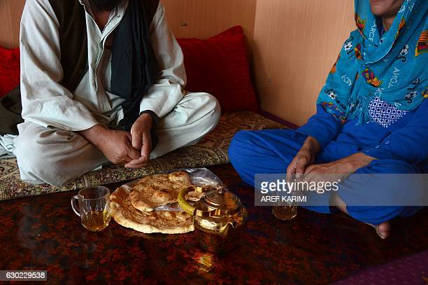 This photograph taken on October 31, 2016 shows an Afghan boy , who was held as a child sex slave, as he prepares to eat with a relative at a...