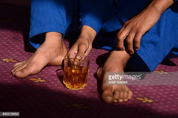 This photograph taken on October 31, 2016 shows an Afghan boy, who was held as a child sex slave, drinking tea at a restaurant in a unidentified...
