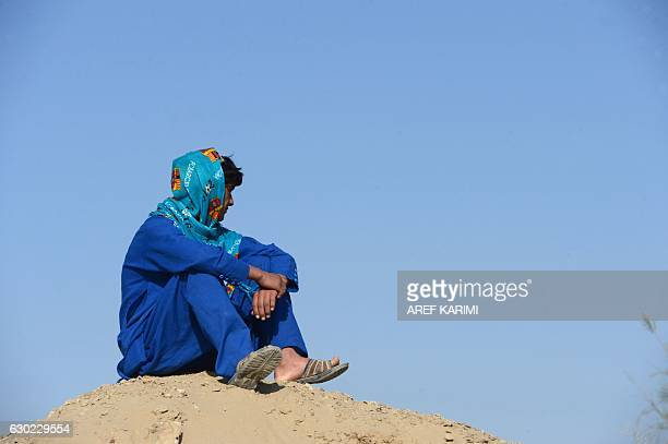 This photograph taken on October 31, 2016 shows an Afghan boy, who was held as a child sex slave, as he sits at a unidentified location in...
