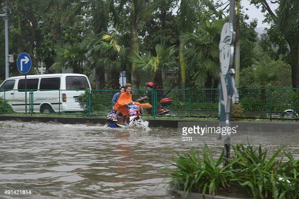 This photograph taken on October 4 2015 shows residents making their way along a flooded street after typhoon Mujigae swept the area in Zhanjiang...