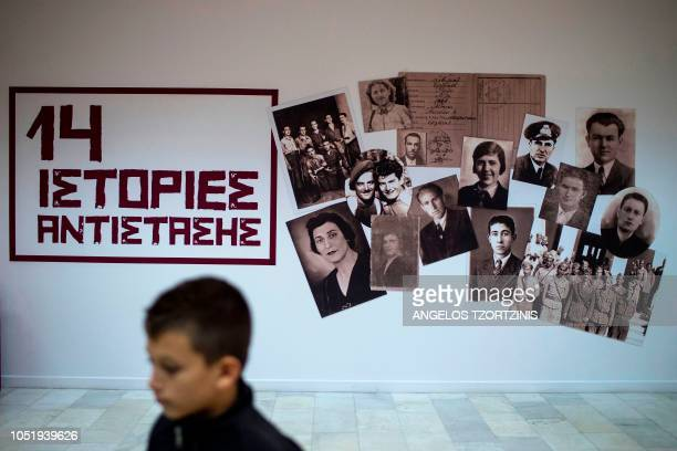 This photograph taken on October 5 shows a visitor walking in front of photographs of the victims of the Nazi occupation during an exhibition...