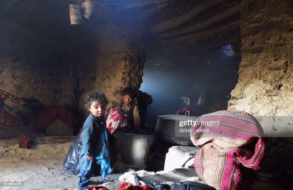 This photograph taken on October 7, 2017 shows Afghan Wakhi nomad children by a stove inside their mud home in the Wakhan Corridor in Afghanistan. The region is so remote that its residents, known as the Wakhi - a tribe of roughly 12,000 nomadic people who populate the area - are untouched by decades of conflict devastating their country. / AFP PHOTO / Gohar ABBAS / TO GO WITH Afghanistan-Wakhan-Taliban-war,FEATURE by Gohar Abbas