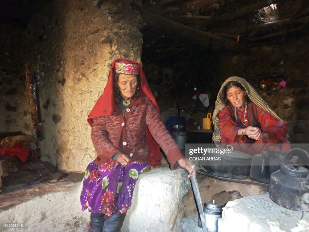 This photograph taken on October 8, 2017 shows Afghan Wakhi nomadic woman Sultan Begium (L) and her daughter-in-law preparing food inside their mud home in the Wakhan Corridor in Afghanistan. The region is so remote that its residents, known as the Wakhi - a tribe of roughly 12,000 nomadic people who populate the area - are untouched by decades of conflict devastating their country. / AFP PHOTO / Gohar ABBAS / TO GO WITH Afghanistan-Wakhan-Taliban-war,FEATURE by Gohar Abbas