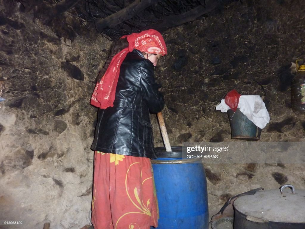 This photograph taken on October 8, 2017 shows an Afghan Wakhi nomadic girl making yak butter inside her mud home in the Wakhan Corridor in Afghanistan. The region is so remote that its residents, known as the Wakhi - a tribe of roughly 12,000 nomadic people who populate the area - are untouched by decades of conflict devastating their country. / AFP PHOTO / Gohar ABBAS / TO GO WITH Afghanistan-Wakhan-Taliban-war,FEATURE by Gohar Abbas