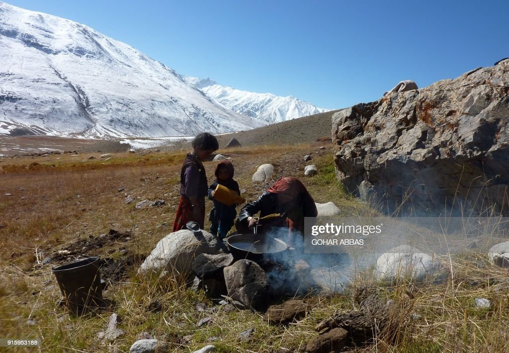 This photograph taken on October 8, 2017 shows an Afghan Wakhi nomadic women warming water outside her mud home for washing clothes in the Wakhan Corridor in Afghanistan. The region is so remote that its residents, known as the Wakhi - a tribe of roughly 12,000 nomadic people who populate the area - are untouched by decades of conflict devastating their country. / AFP PHOTO / Gohar ABBAS / TO GO WITH Afghanistan-Wakhan-Taliban-war,FEATURE by Gohar Abbas