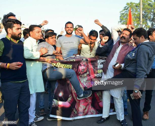 This photograph taken on on January 24 2018 shows protesters kickicking the a film poster of Bollywood film 'Padmaavat' during a protest against the...