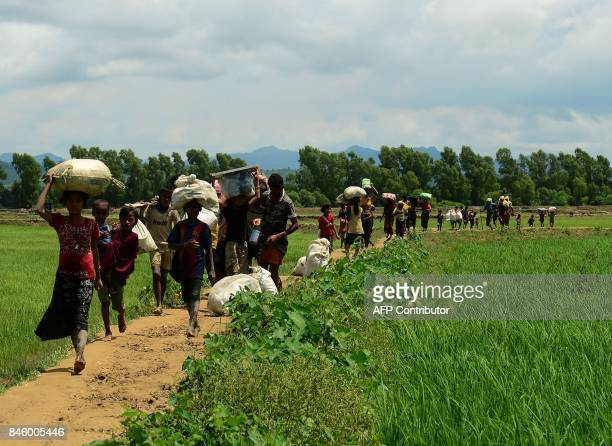 This photograph taken on September 11 2017 shows Rohingya Muslim refugees arriving from Myanmar through Lomba Beel after crossing the Naf river near...
